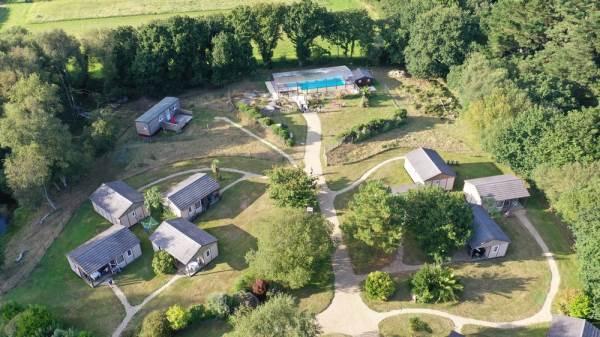 Des chalets dispersés dans un parc avec jeux de plein-air, piscine couverte.