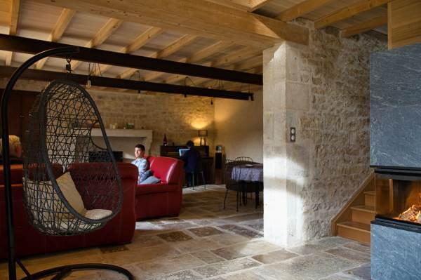Espace entrée, salon, salle à manger avec : - un poêle à bois semi-masse ; - un espace salle à manger (table extensible) ; - salon composé de 2 canapés, - espace bureau ; - 1 fauteuil suspendu (loveuse)