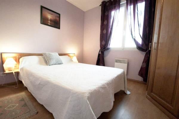 La chambre parme, un lit de 140 pour 2 personnes et une armoire avec penderie et étagère