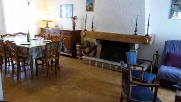 Le coin salon- salle à manger et sa cheminée.Gîte Le Malaval - Maison de charme au coeur du parc du Vercors.