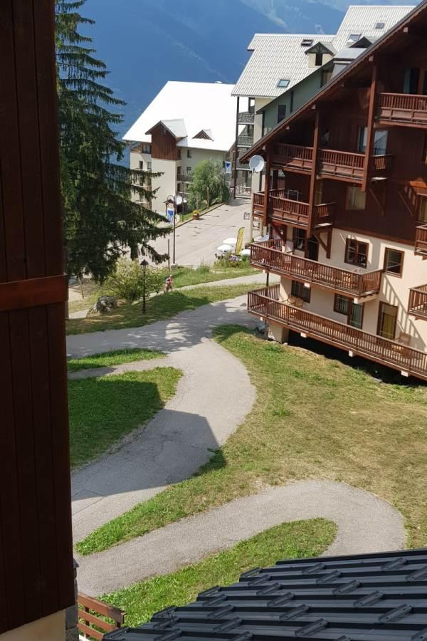 Depuis l'entrée de l'appartement B11, vue sur le chalet de réception ainsi que sur le départ de l'ESF (Ecole de Ski Française)