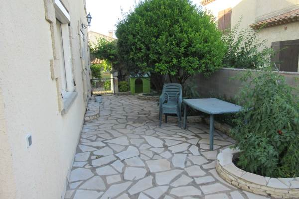 Terrasse avec salon de jardin entre le mandarinier et l'olivier et la cabane pour enfants